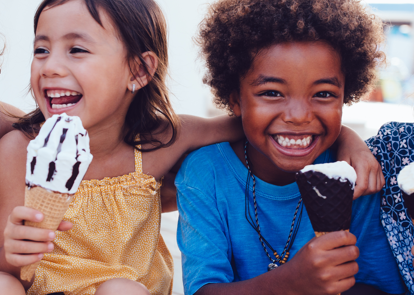 multiple kids sitting and eating ice cream